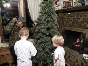 Helping daddy walk around and around the tree, putting up the lights.
